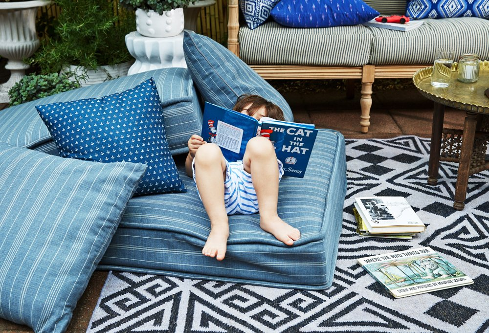 Day's three-year-old son, Arthur, gets comfy with a few good books on oversize floor cushions covered in a striped outdoor fabric by Perennials.