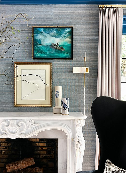 Lynn took a curatorial approach when styling the mantel.The abstract art mixes beautifully with the more traditional seascape. The ceramic vases also play nicely off the handcrafted sconces by ceramicist John Sheppard. Moments like these really bring the design to life.