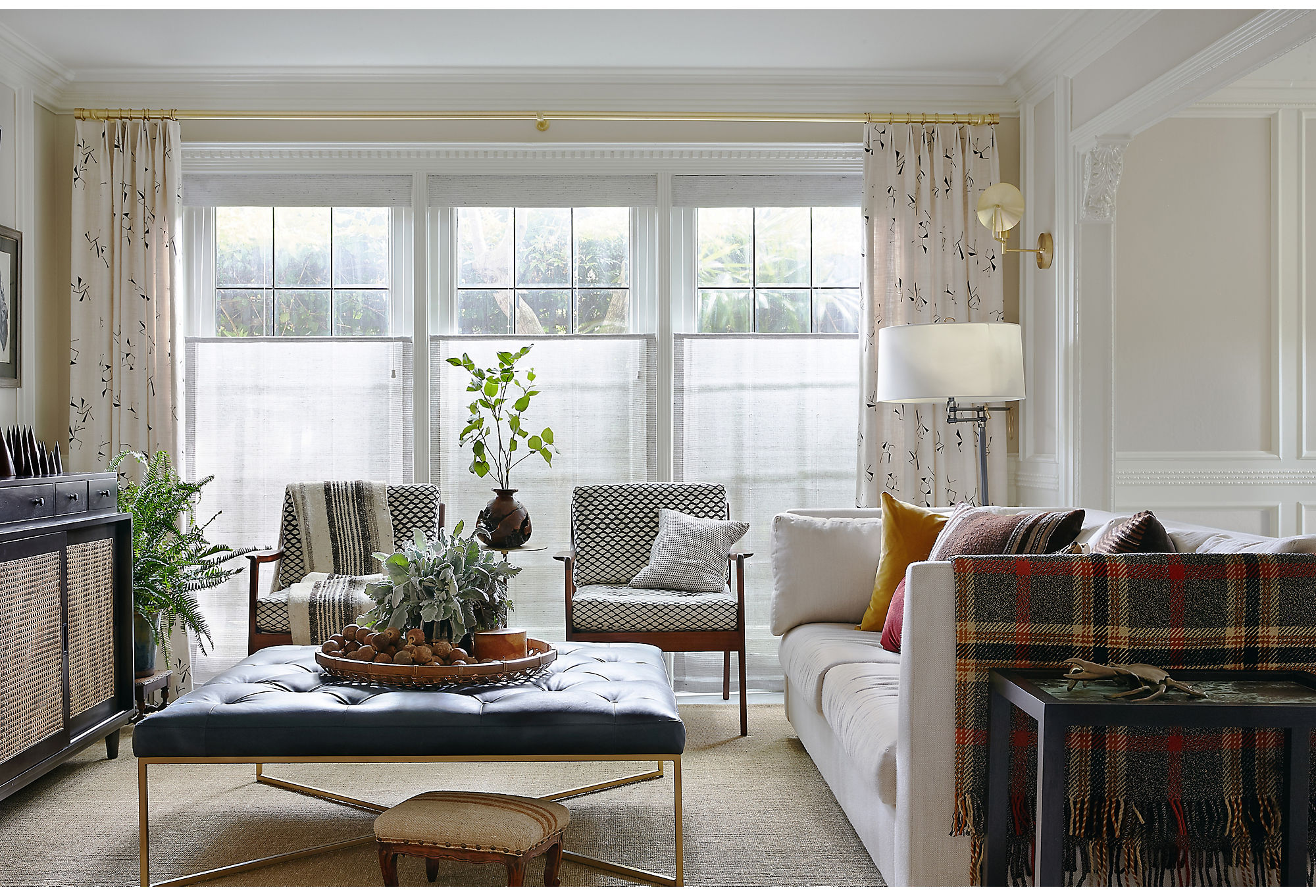 The family room went neutral in color but poppy in pattern. Lynn kept things low-key by choosing creams and whites but complemented the color withinviting patterns on the drapes and accent chairs.