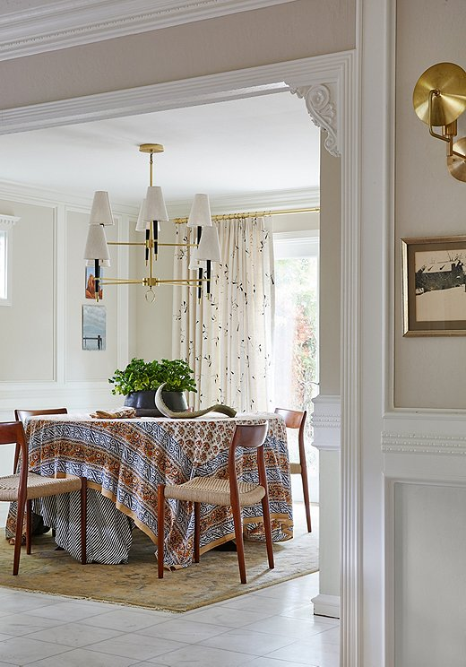 Lynn went neutral with the diningarea. A block-printed tablecloth added a pop of pattern to the space. A gold chandelier with linen shades makes a statement over the table.