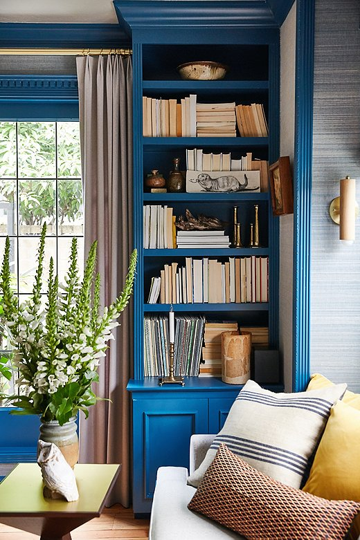 Lynn let the blue color palette do the work in the formal living room. She turned books around to let the worncolor of the pages work symbiotically with other natural elements. She relied on the pillows to bring out the room's complementary colors.