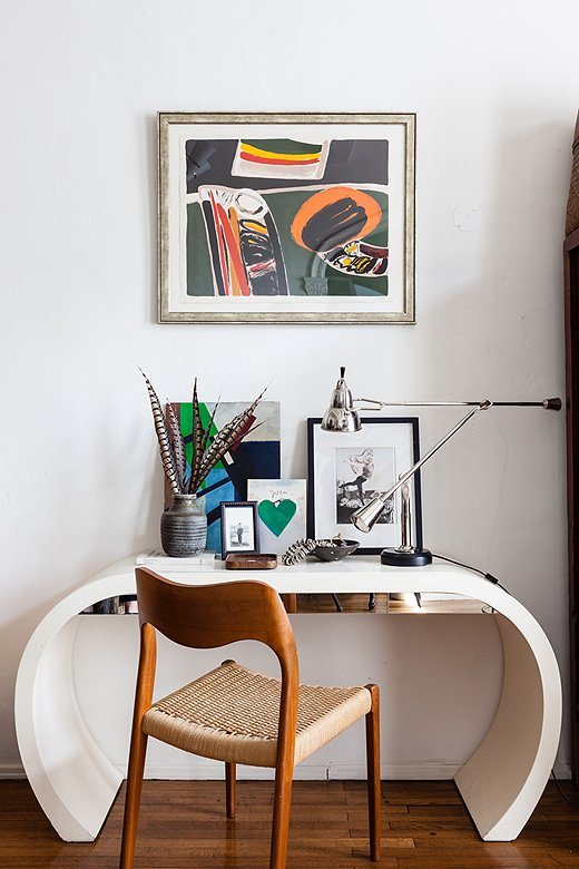 Colorful art, a gleaming lamp with a polished nickel finish, and the mirrored drawer fronts of the desk disrupt the neutral color scheme to beautiful effect. Photo by Nicole LaMotte.