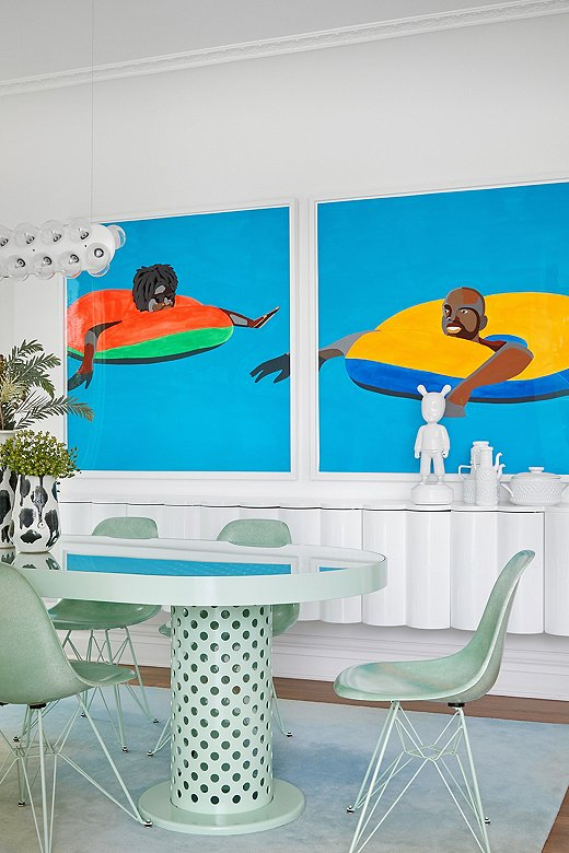 The creamy seafoam dining set plays against the bright bold colors in the diptych by Derrick Adams that hangs behind it.