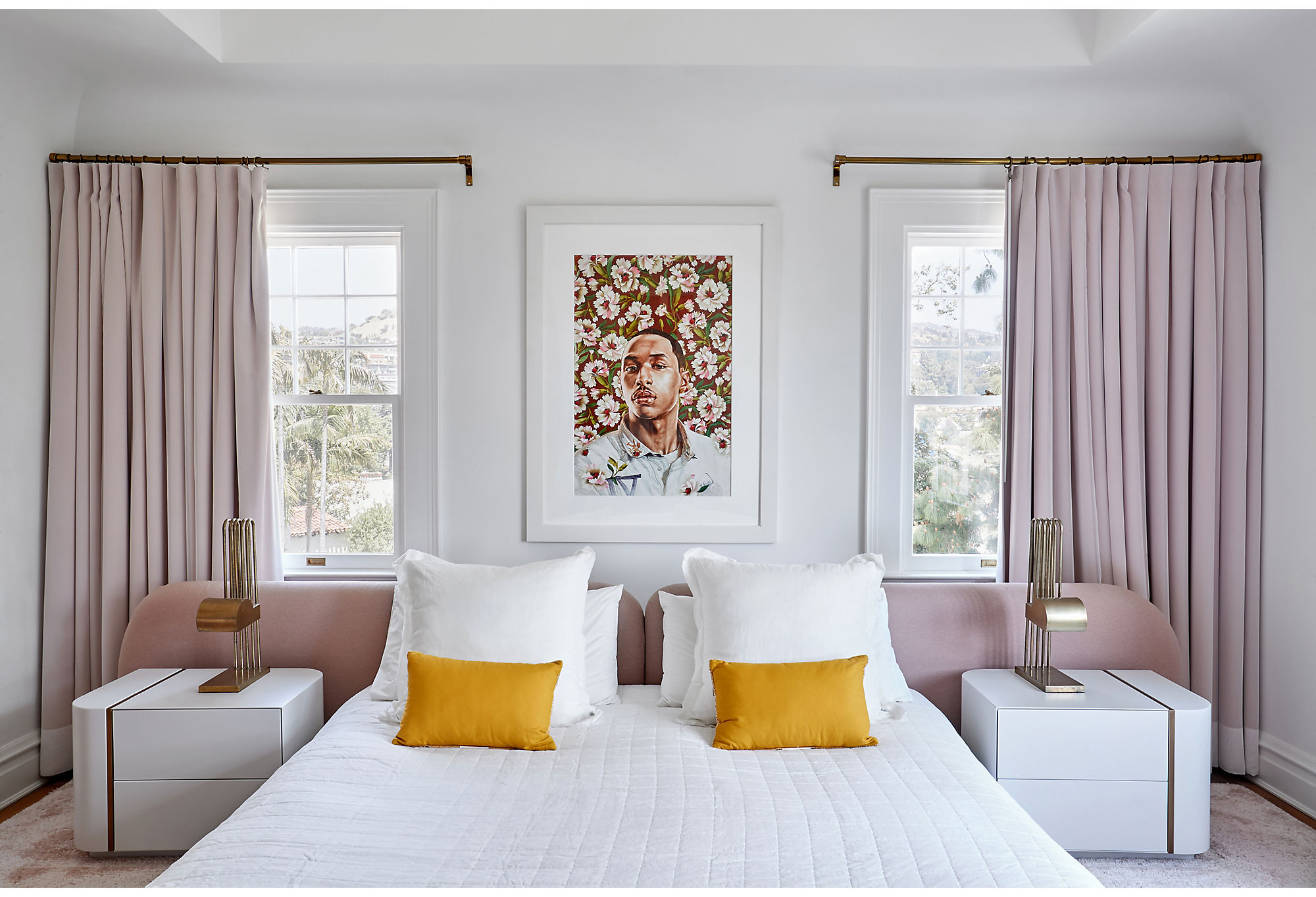 A portrait by Kehinde Wiley hangs over a custom bed designed by Ghislaine.