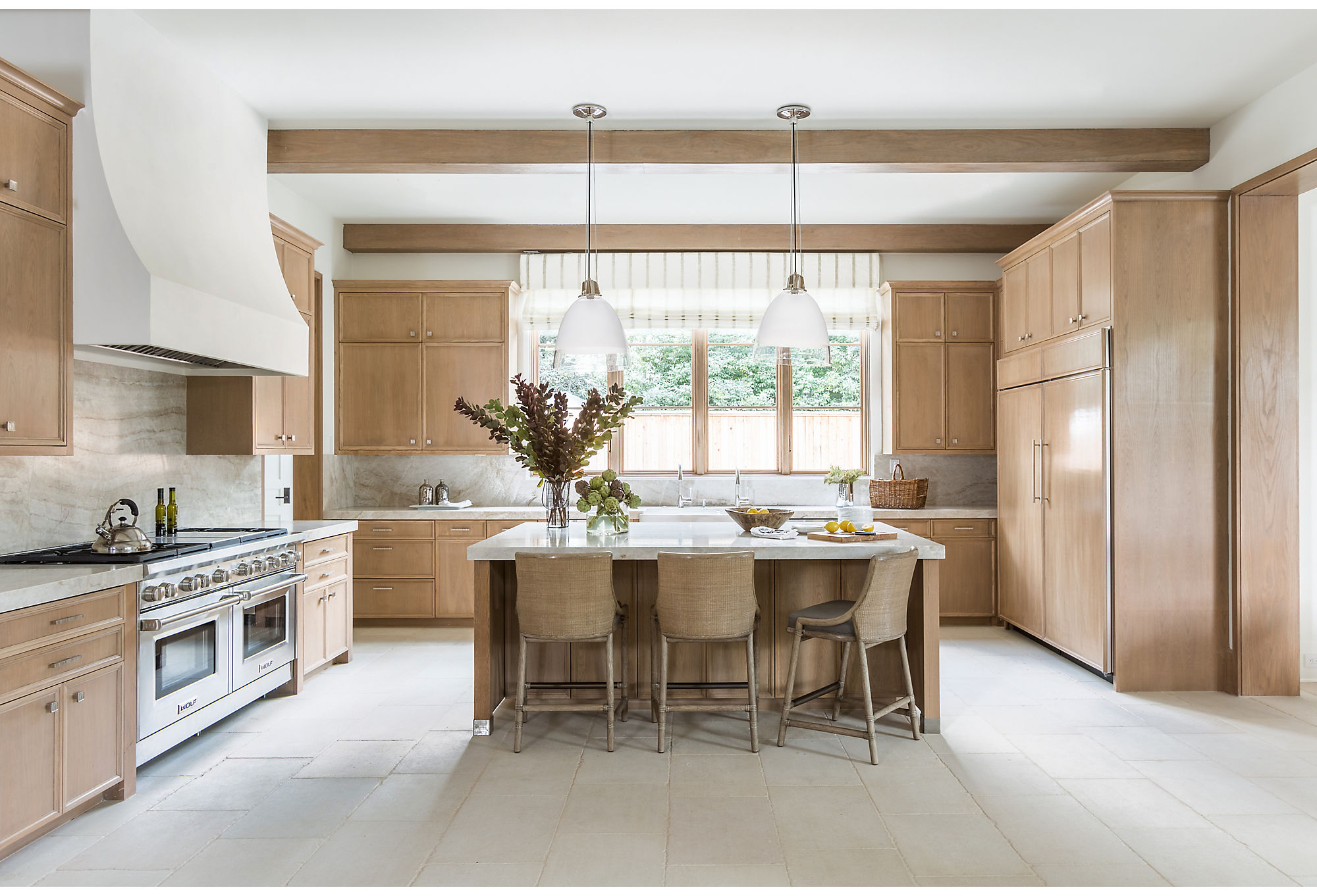 """They're a family who uses their kitchen quite a lot,"" says Marie. In keeping with the simplistic elegance throughout the home, Marie and her team went for  a subdued palette. Subtle caramel tones and spots of brushed nickel make the heart of the home shine."