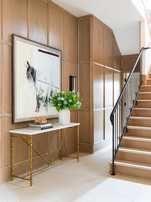 The panel-work in the staircase showcases the raw beauty of the rift-cut oak. The console table's gilded legs introduce a graphic and geometric moment to the space.