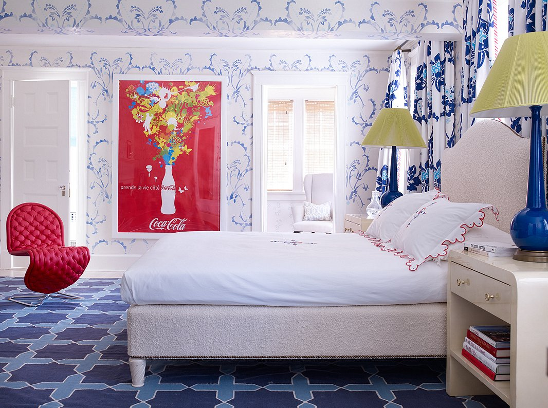 Designed for one of the family's children, this bedroom features hand-stenciled walls. The French Coca-Cola poster and the curvy red chair ensure that the room doesn't feel overly traditional.