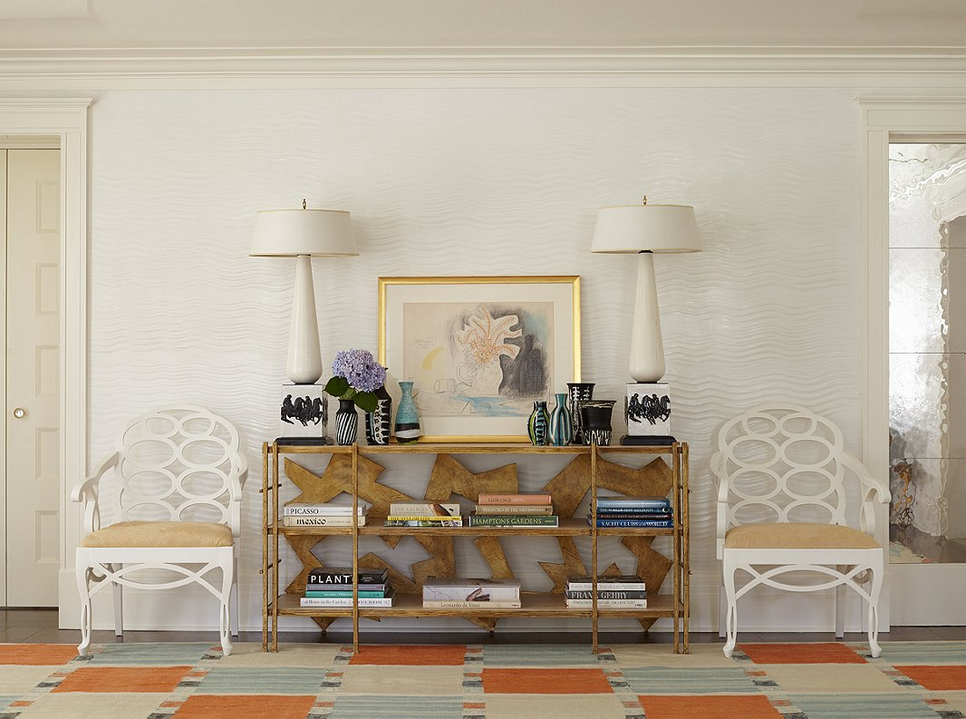 "The Swedish rug, custom-made to accommodate the spacious living room, inspired the sky-blue-and-orange palette. Custom textured plaster adds subtle pattern to the space. Iconic Loop chairs by 20th-century designer Frances Elkins, seen above, also encircle the two dining room tables. The chairs ""are always a nice complement to traditional interiors, making them feel more current,"" Stewart says."