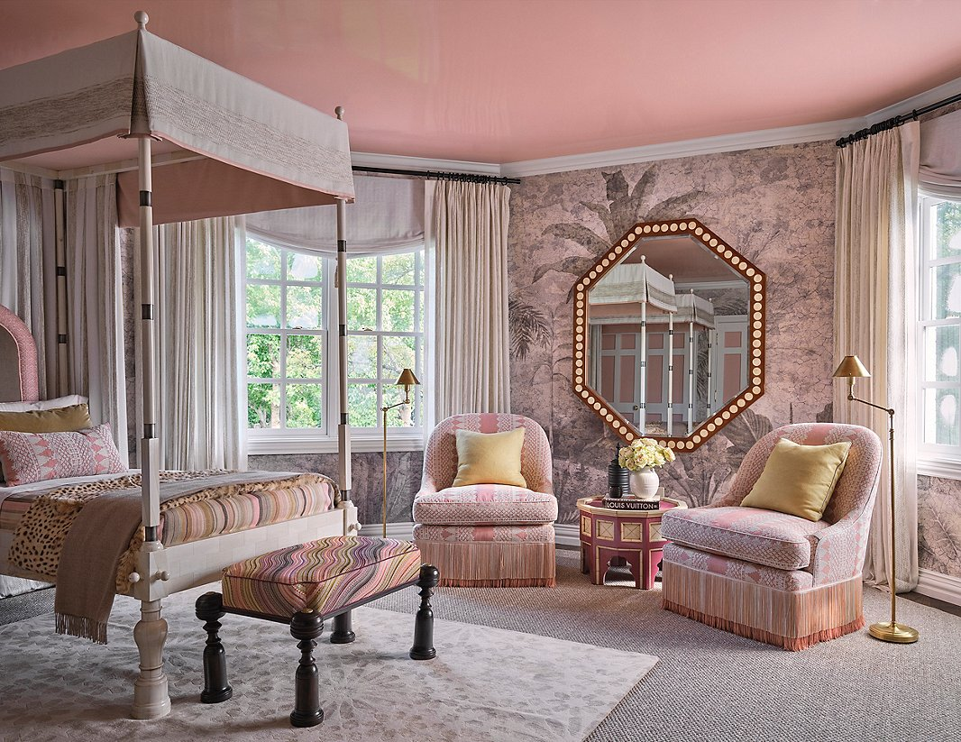 """Jaipur, nicknamed the Pink City for the color commonly seen on its buildings, was one of Martyn Lawrence Bullard Design's inspirations for this en-suite guest bedroom. The """"think pink"""" theme extends up to the lacquered ceiling. Syrian side tables and a Moroccan rug, among other pieces, give this space globe-trotting flair. Photo by Stephen Karlisch."""