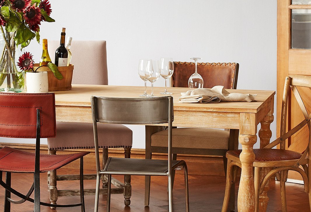 Why match when you can mix? Not only are the chairs different styles, but they're also made of different materials. The brown-and-beige palette keeps the look cohesive. And what could be more Mediterranean than using a rustic basket to hold a few bottles of wine?