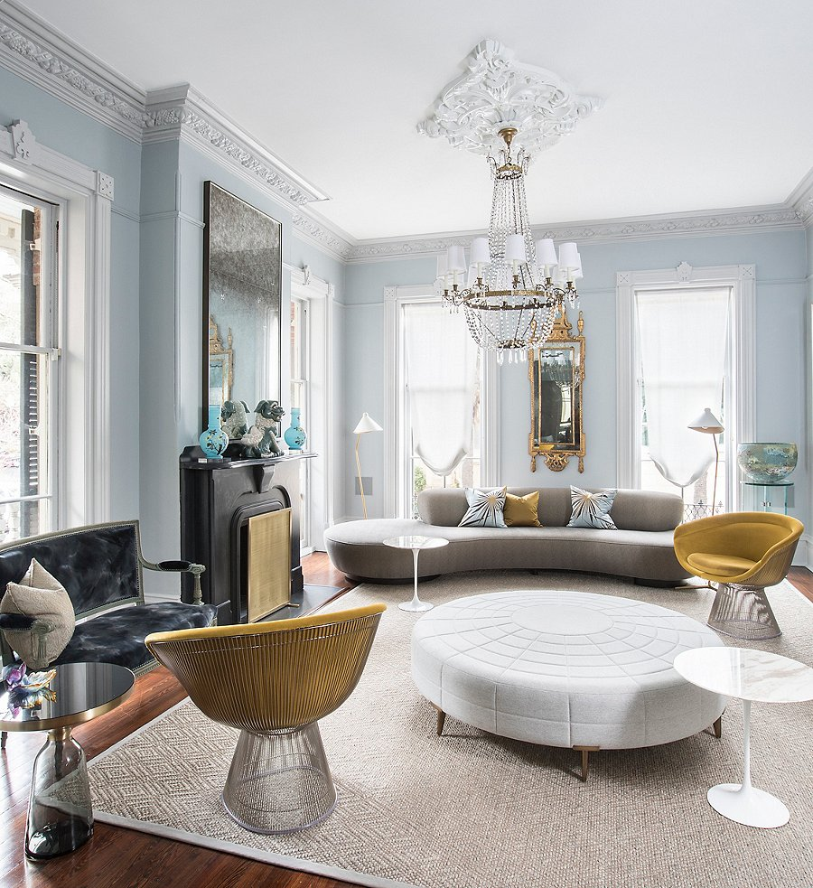 """""""We wanted everything in the house to be loungy and comfortable, especially the upholstery, like the giant white ottoman in the middle of the living room that you can just perch or lie on,"""" says Chuck. With a combination of traditional touches such as the 19th-century chandelier and more-modern furnishings such as Saarinen side tables and the Vladimir Kagan for Ralph Pucci sofa, the space radiates an eclectic, timeless energy."""