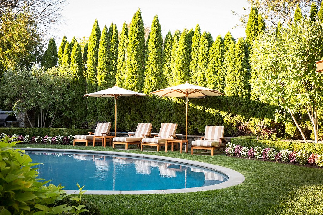 Surrounded by tall trees and manicured hedges, this poolside feels like a true oasis. Photo by Lesley Unruh.