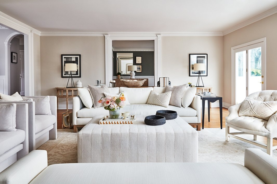 An upholstered ottoman by Tammy Price anchors the living room and is a kid-friendly alternative to a sharp-cornered coffee table. Vintage cable-knit pillows and a pair of woven baskets lend an extra hint of texture to the neutral scheme.