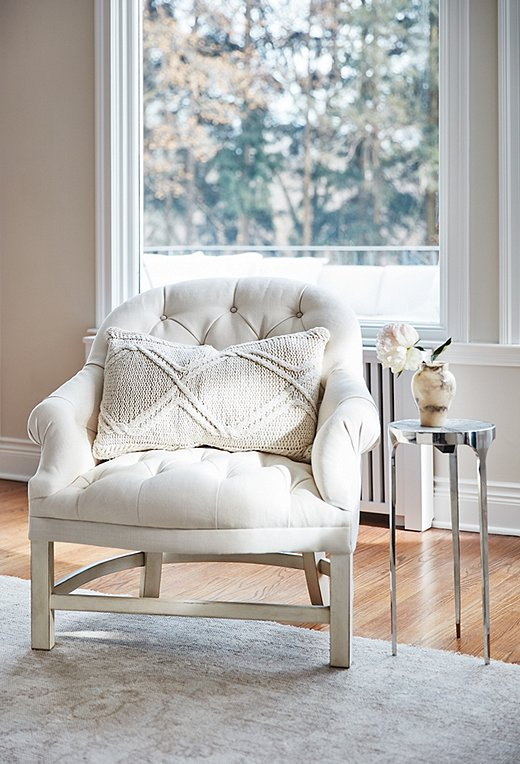 "A tufted Bunny Williams chair basks in the sunshine. ""If I find myself with a quiet moment, I go sit there,"" Emily says. ""It's right by the window, so I'm getting the natural light. It's a zen place for me."""