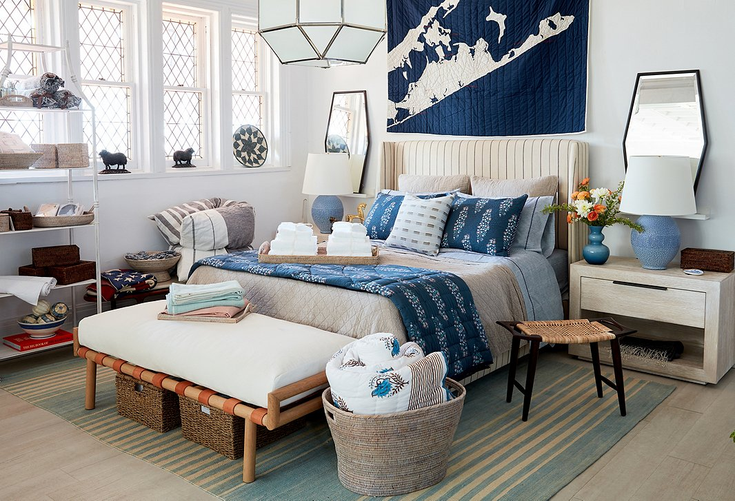 In the bedroom, neutral furnishings (a striped bed, the Vander bench by Community, a whitewashed nightstand) are livened up with blue accents (quilts by Haptic Lab and Roller Rabbit and table lamps by Aerin).