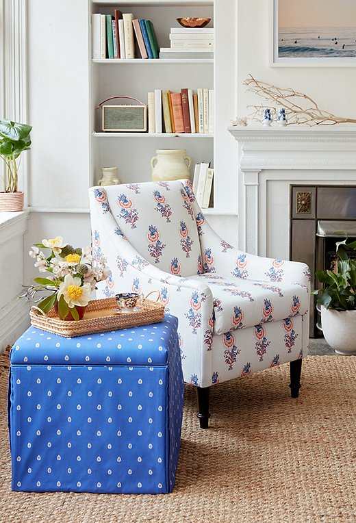The larger scale of the Desert Flower print in lapis/coral on an accent chair pairs perfectly with the petite dots of the Mariposa skirted storage ottoman.