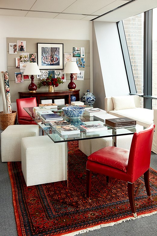 "A set of petite ottomans and a pair of Ralph Lauren Home Lawson Chairs, upholstered in red leather, surround the glass conference room table. Against the windows, a linen settee offers an additional spot to sit during meetings or to work solo. ""The idea that you can sit in the middle of the day, have a view of Central Park, and maybe have a few sips of coffee is comforting,"" Stellene says."