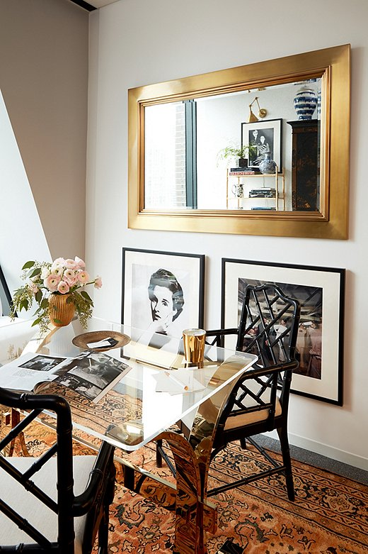 "Opposite the secretary, the oversize Duke Mirror from Ralph Lauren Home hangs above prints from the magazine's vast photo archives. The portrait of Babe Paley (at left)—who Stellene calls one of the ""quintessential modern swans""—is by famed photographer Richard Avedon."