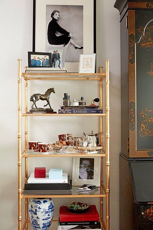 "Stellene's daily essentials and personal mementos fill the gilded étagères flanking the secretary, including fragrances from Frédéric Malle (""I'm never far from a bottle of Promise or Portrait of a Lady,"" she says), a tea set gifted by Ralph Lauren Home when she became editor-in-chief, copies of her book on jewelry, and framed family photographs."