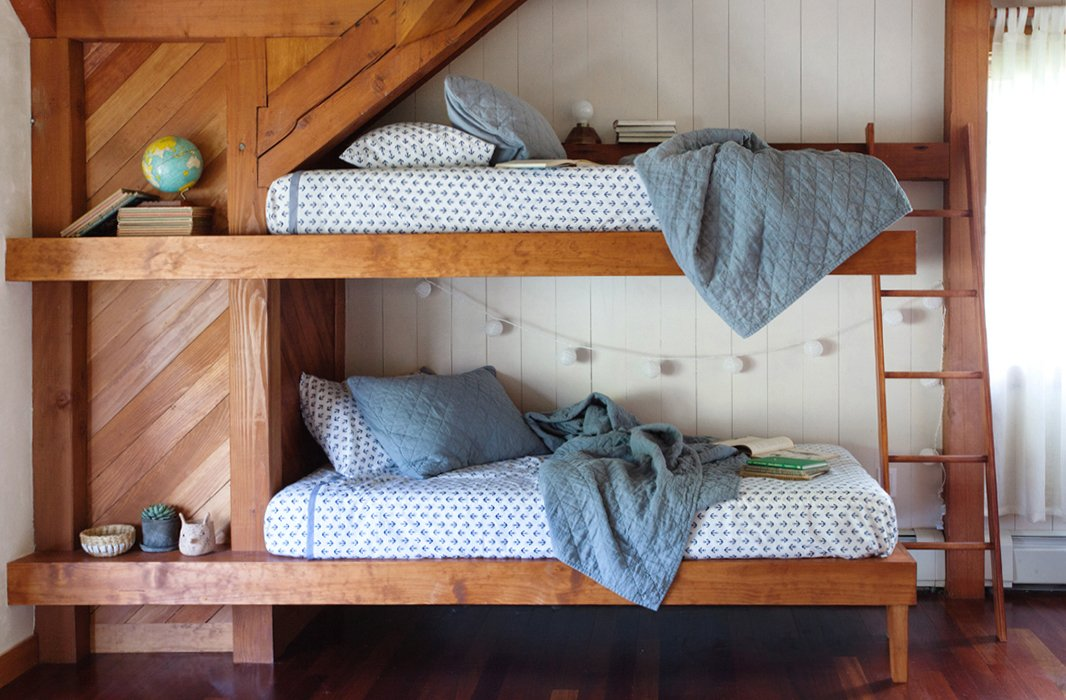 Percy built custom bunk beds for the bedroom of the two eldest boys, where simple blue quilts add a cozy and charming complement to the austere wood beams.