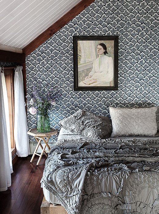 In a guest bedroom, beautifully ruffled and textured bedding takes center stage, and the effect is repeated in the Farrow & Ball Aranami wallpaper. The painting, one of Tara's favorite finds for the home, is from Brimfield.