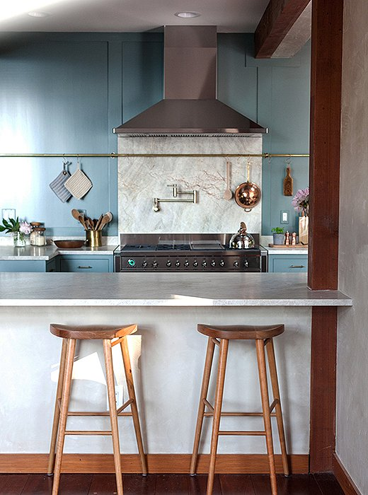 Quartzite, which Tara and Percy chose for its striking texture, was used for the counters and the backsplash installed above a Smeg range. The kitchen is painted in Benjamin Moore's Porch Swing.
