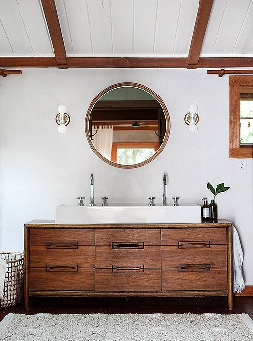 The light-filled bathroom, originally covered in tiles, was given plaster walls to brighten up the large space. The custom sink vanity was a vintage dresser that Percy revamped.