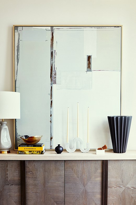 Layering without creating clutter, especially in small spaces, takes a keen eye. Becca opted for one unique candleholder rather than a grouping atop the sideboard. Adding in books, objets, and lamps of various heights is a smart way to entertain the eye.