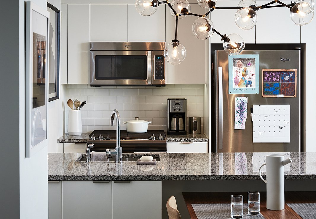 The kitchen required little in the way of dressing up. It is accented with a constellation-inspired chandelier and a few pieces of art. In lieu of barstools, they tucked the dining table under the counter to create enough space for four to sit, eat, or do homework.
