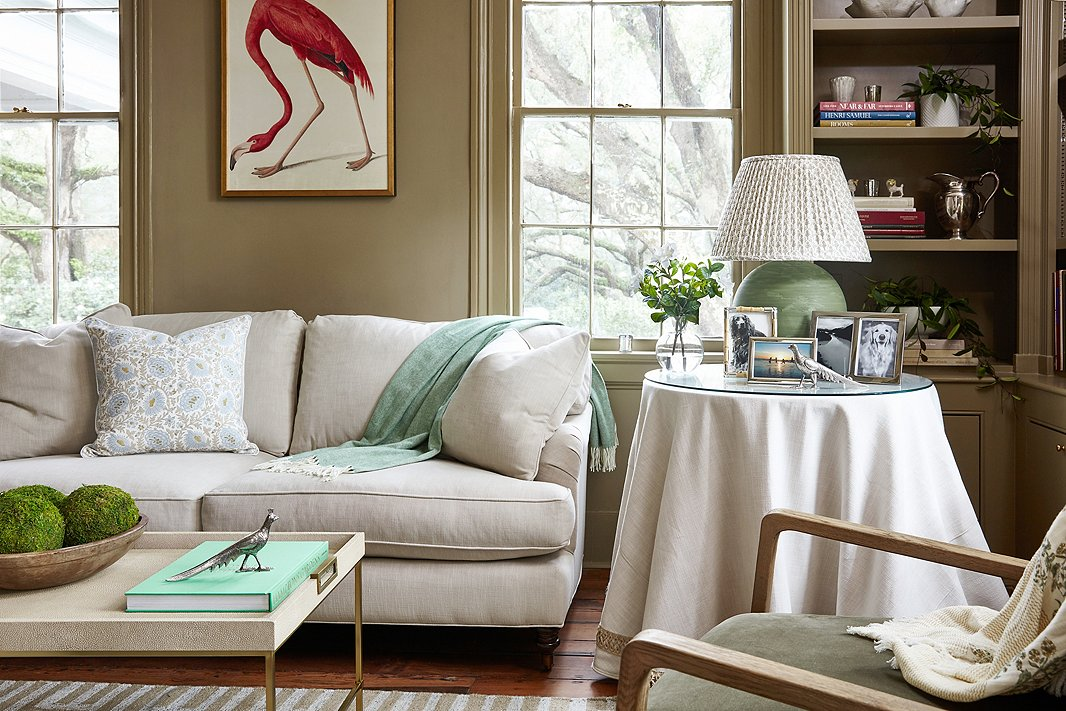Audubon's American flamingo printbringsa pop of color to the room's otherwise quiet palette. Find the sofa here and the skirted table here.