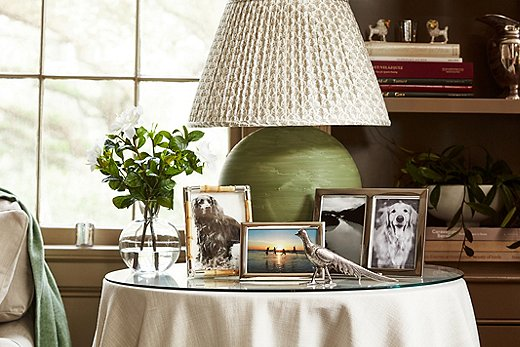 A pleated patterned lampshade, a skirted table, flowers, and framed photos of dogs: the epitome of English cottage style. Photo by Frank Tribble.