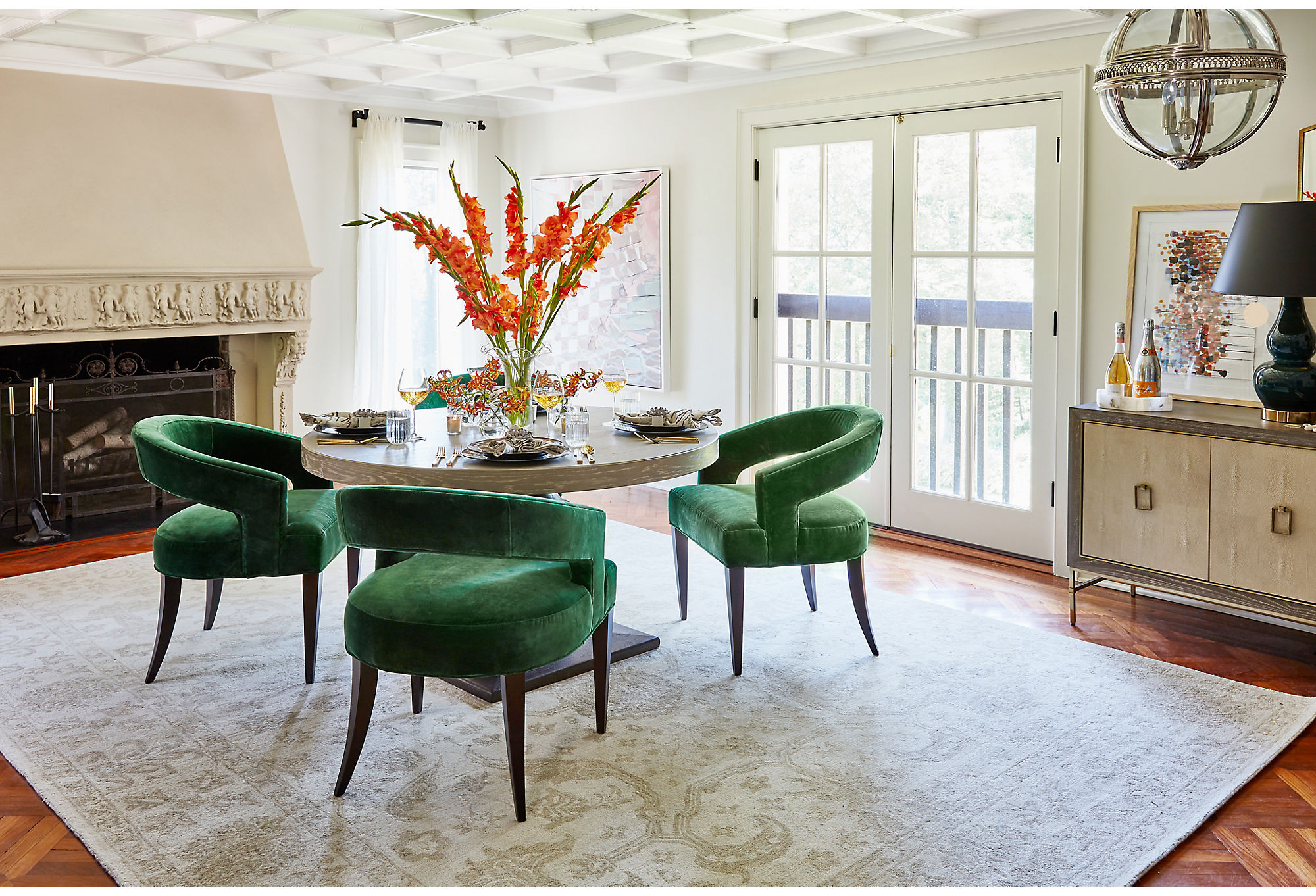 The rich color and modern silhouette of the Ella Accent Chairs in Emerald Velvet provide a dynamic contrast to the serenity of the neutral traditional rug. The chairs' curves also complement the straight lines of the Lexi Sideboard.