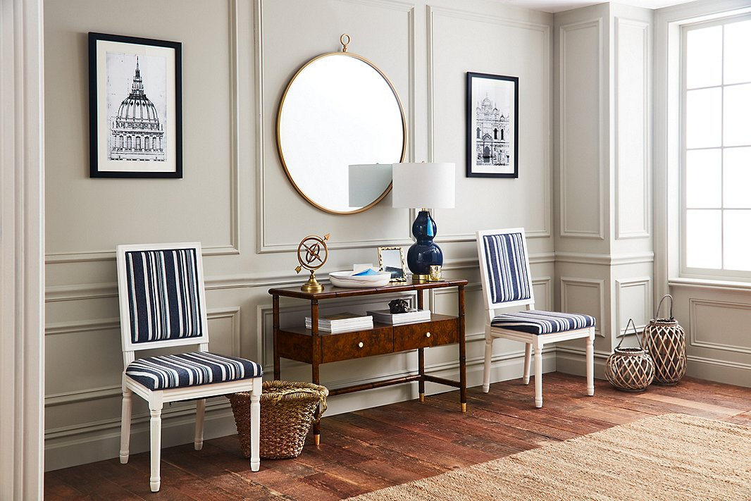 With a tabletop, a shelf, and two drawers, the Huntley console offers a wealth of storage—and at 42 inches wide, it's well suited for small and larger spaces alike. Here it is flanked by Calais side chairs upholstered in a tailored stripe. The frame of the round Beatrix mirror accentuates the gold tones of the console's ferrules and drawer knobs.