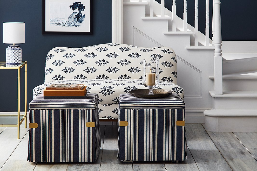 The well-edited palette of Open House makes it easy to mix patterns for a rich layered look. Case in point: the Eleanor camelback settee in indigo sprig, the blue-and-white striped Squires ottomans, and sitting atop the Huntley bar cart, the Archer table lamp.