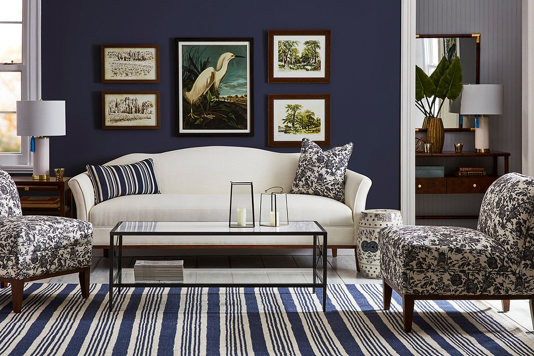 In addition to furniture, One Kings Lane Open House includes lamps, mirrors, pillows, and even art, such as the pieces above. Resting on the Eleanor camelback sofa in ivory are the Alana lumbar pillow in blue-and-white stripes and the Maura pillow in the same gray toile as the Eleanor slipper chairs. The striped Shani rug in indigo/ivory ties everything together.