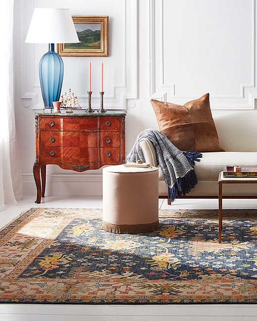 Ottomans can serve as side tables too. An added advantage of a small round ottoman like this one is that it provides complementary curves to a room dominated by straight lines.