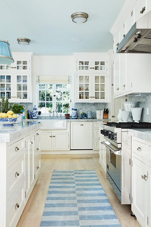 Mark Sikes chose to paint the ceiling of this kitchen a light blue. He carried the color throughout the space with ginger jars, a blue shade on the pendant light, and a blue runner.