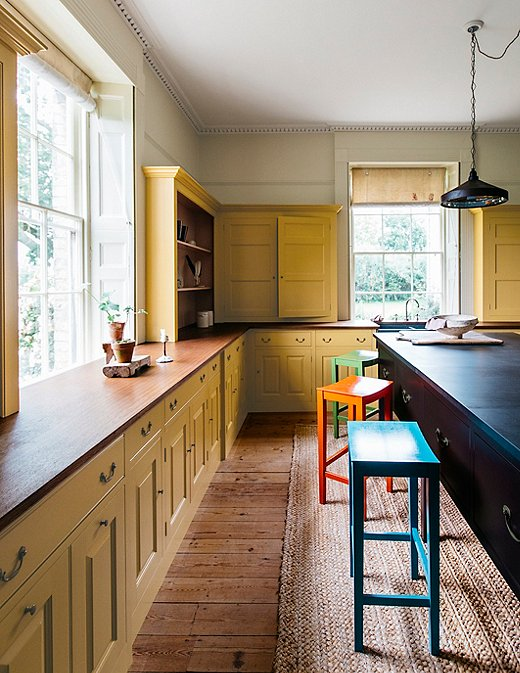 This kitchen takes a next-level approach to color by painting the cabinets in Nicotine and dotting stools painted in Tea Caddy, Medlar Jelly, and Moygashel throughout the room.