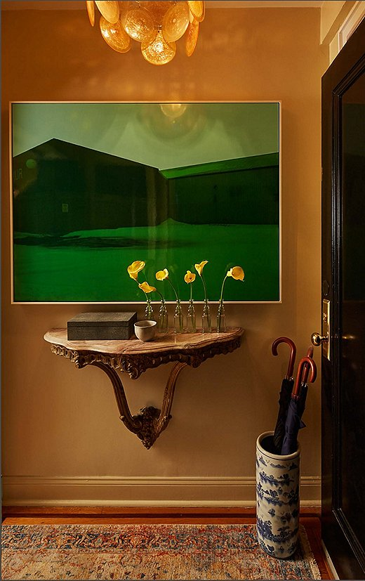 """We tried to make it a moment,"" Philip says of the apartment's petite entry. ""The acid-green painting is shocking when you open the door, but it's only for a second, and then you move into the rest of the space."" The art contrasts with the marble-top French console below, on which a faux-shagreen box holds keys and dog leashes to be quickly grabbed before walking out the door."