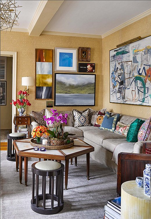 The custom sofa and sectional in the living room are dressed in neutral fabrics to accommodate a host of mix-and-match pillows, which include embroidered vintage finds along with designs from Bunny Williams Home and Brunschwig & Fils.