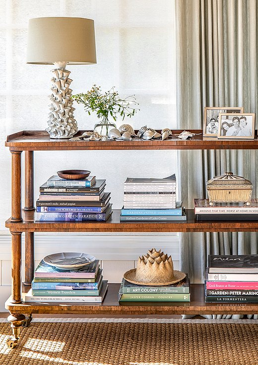 Antique pieces of furniture were the perfect solution for a space that needed smaller silhouettes. This antique étagère houses the client's collection of silver-plated shells.