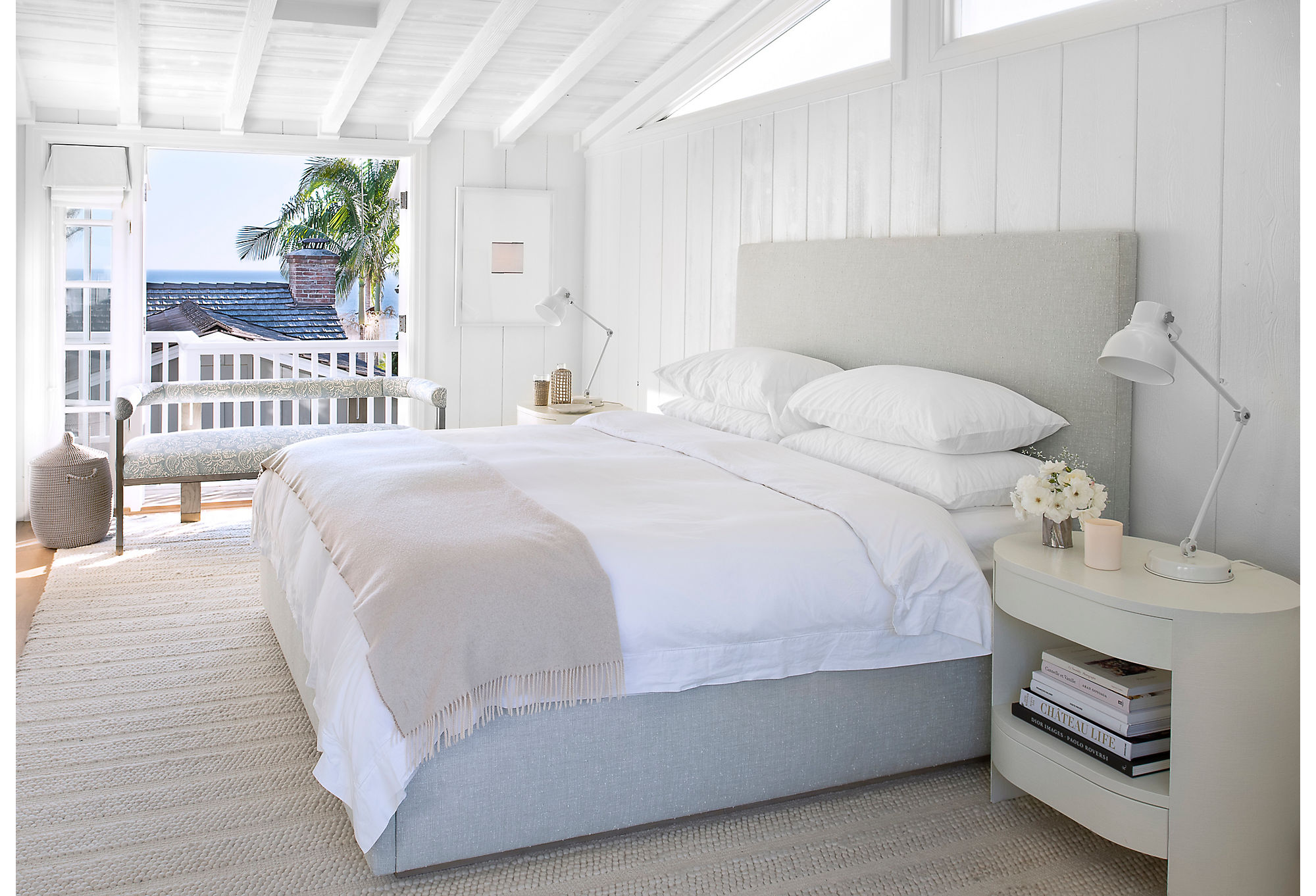 """""""We were going for a spalike atmosphere,"""" says Marea of the main bedroom. Bright light floods the shiplap-laden room. A custom wool rug provides comfort underfoot. """"The pattern is almost like a fisherman's sweater,"""" says Marea. The bed, upholstered in blue linen, is also custom."""