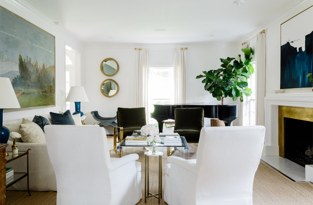 The large-scale European landscape painting in the living room served as a jumping-off point for the entire design scheme. A sisal rug lends a casual feeling to the space, contrasting the more-glamorous touches such as the Lucite coffee table and velvet accent chairs.