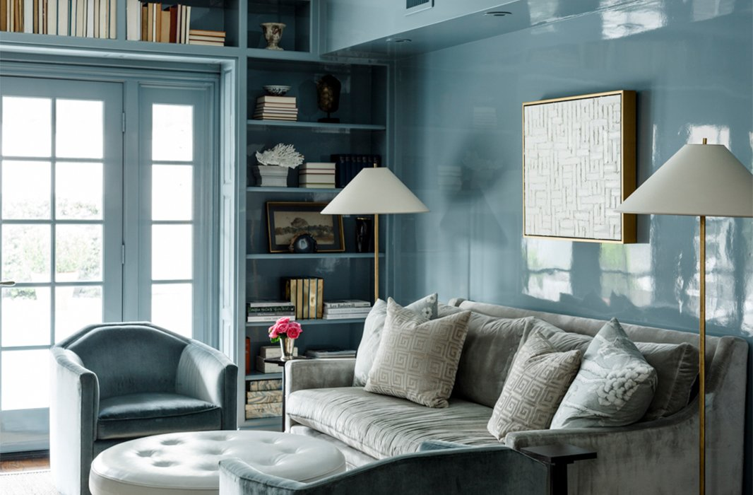 Lacquered in a dreamy blue hue, the home's cozy library features a round leather ottoman in lieu of a coffee table, artfully arranged shelves, and a gray velvet sofa.