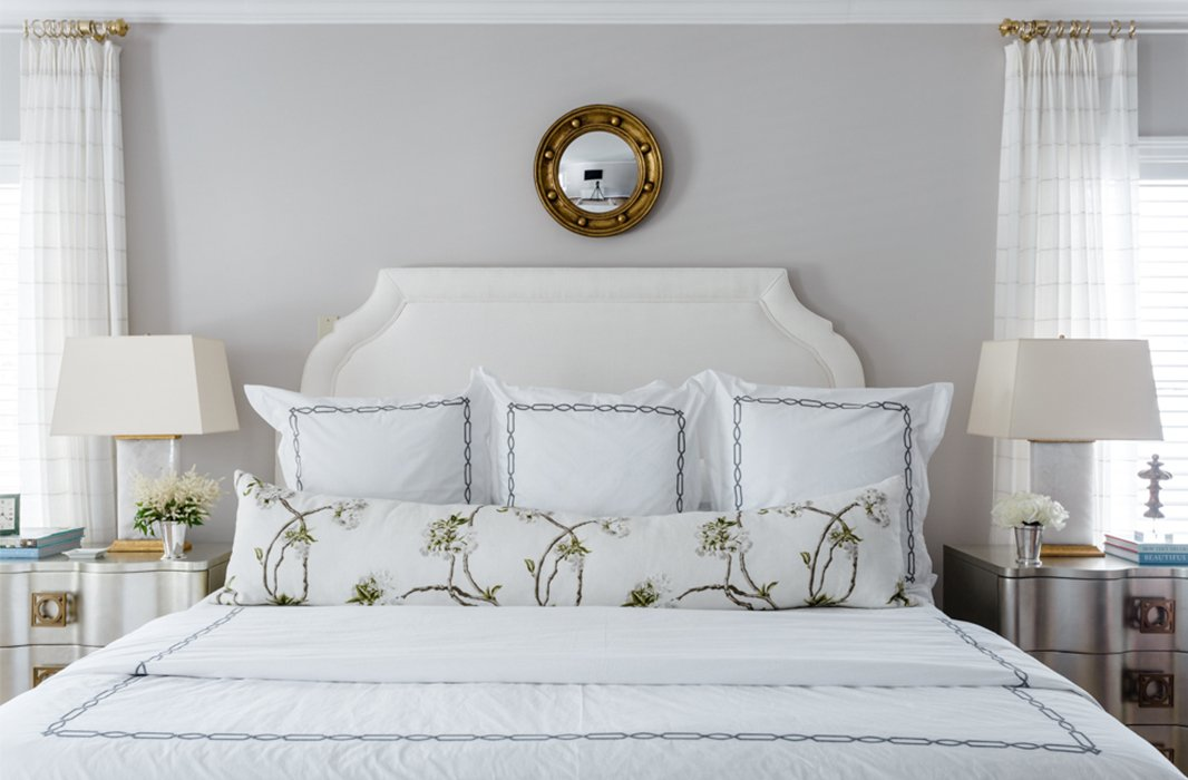 A porthole mirror crowns the upholstered headboard in the master bedroom, repeating the gilded finish found on the quartz lamps.