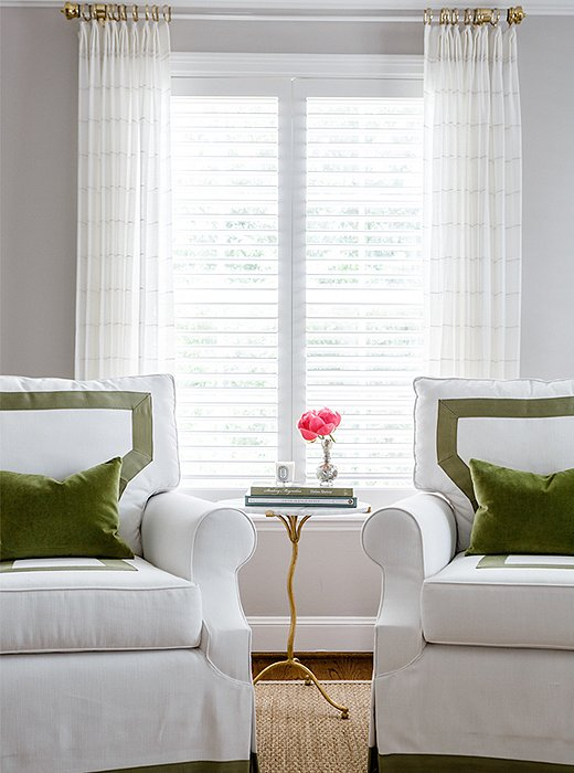 A pair of custom-upholstered armchairs and velvet throw pillows lend a pop of color to the otherwise-neutral master bedroom.
