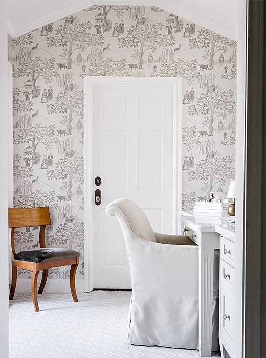 Wallpaper in a gray-and-white pastoral pattern adorns an accent wall in the dressing room.