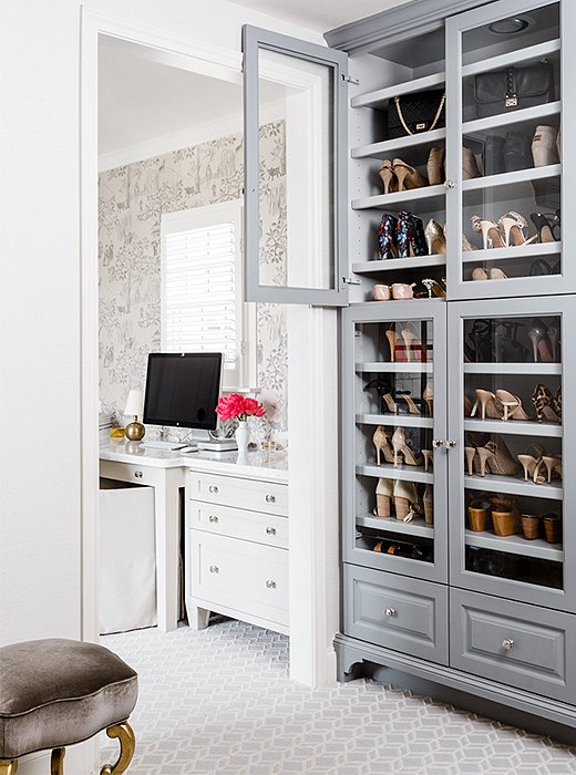 Painted gray for a touch of contrast, a glass-front cabinet in the master closet puts shoes and handbags on display.