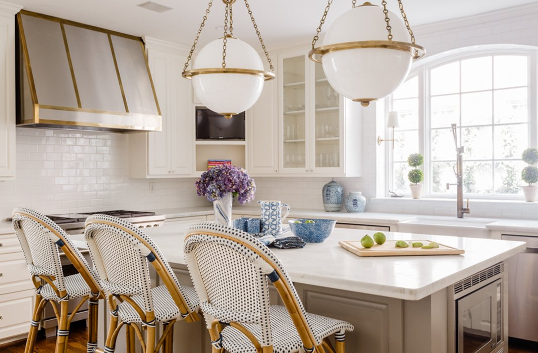 Paloma completely reworked the kitchen's layout during the renovation process. Moving the stove from the island to the wall freed up space for a central worktop and pair of oversize pendants.