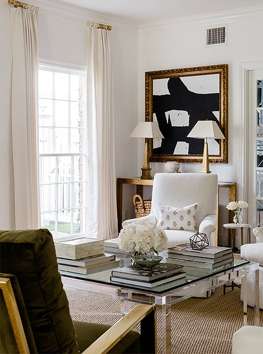 Flanked by a pair of brass lamps, a black-and-white abstract painting speaks to the homeowners' contemporary taste.
